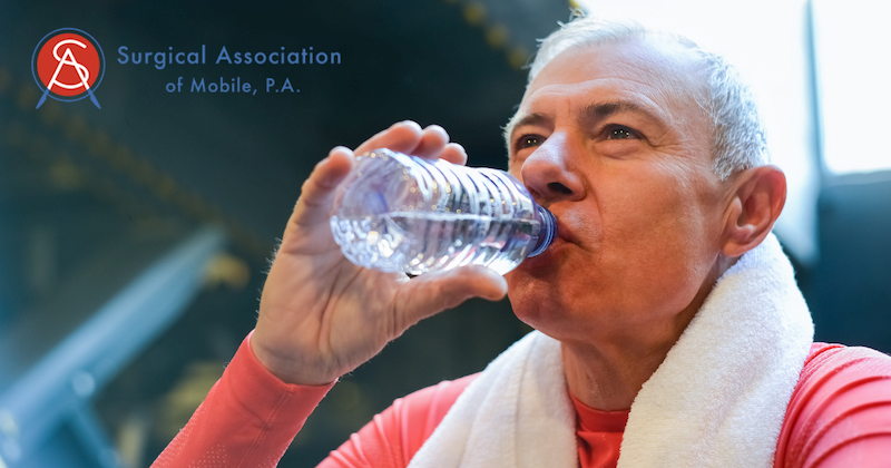 Older Man In Red Shirt with White Towel Around His Neck Drinking Bottled Water